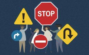 Pessoas seguram placas de trânsito com sinais de risco